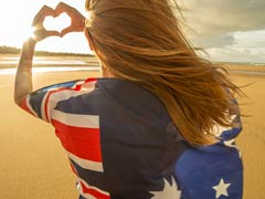 Blonde haired female member on a beach and draped in an Australian flag